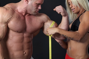 Girl measuring bodybuilders biceps