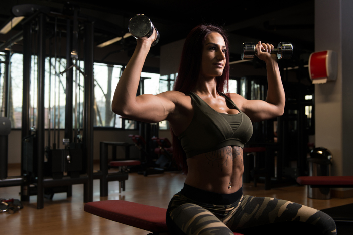 Fit woman doing dumbbell press