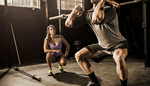 Man performin squats while woman is watching