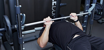 Man performing close grip bench press with Smyth machine