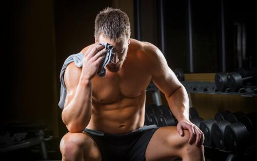 Bodybuilder sitting on bench
