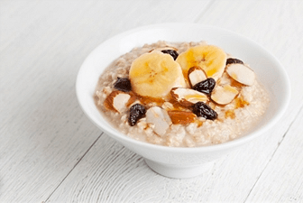 Bowl of cooked oatmeal with fruits and nuts