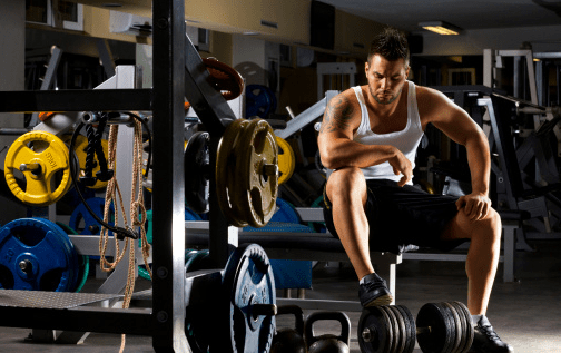 Young man setting on weight bench