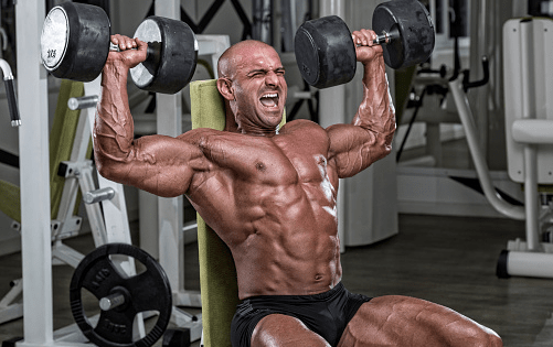 Bodybuilder with no shirt performing dumbbell presses