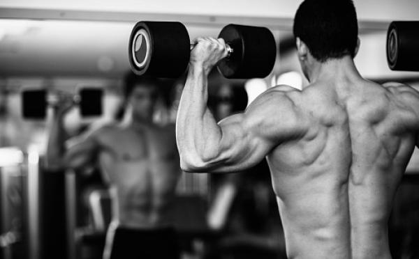 Bodybuilder training with dumbells
