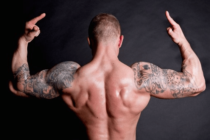 Tattooed bodybuilder Flexing Muscle