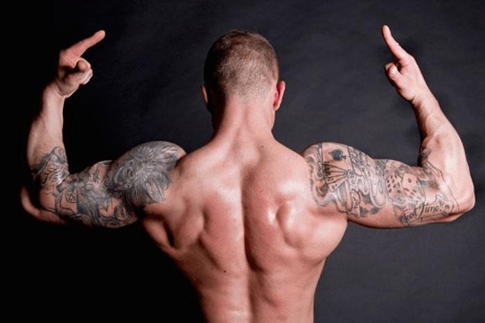 Tattooed bodybuilder Flexing Muscle
