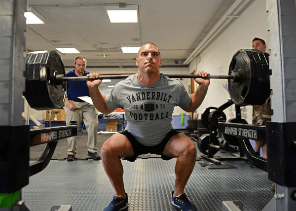 Man Doing Squats with 4 plates on Each Side